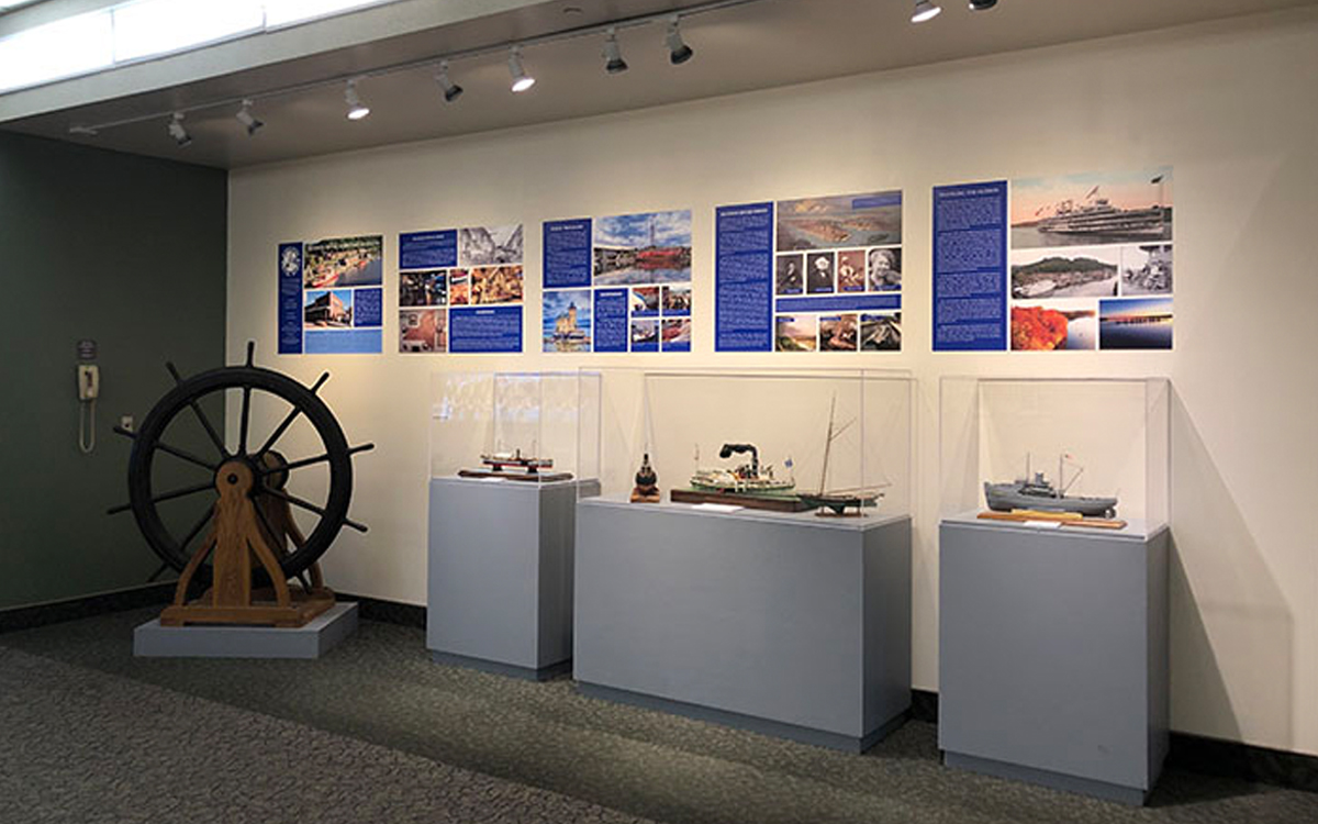 three custom display cases under graphic panels and next to ship's wheel