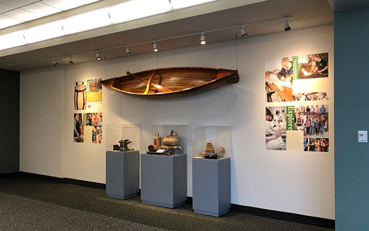 three display cases holding artifacts under hanging canoe