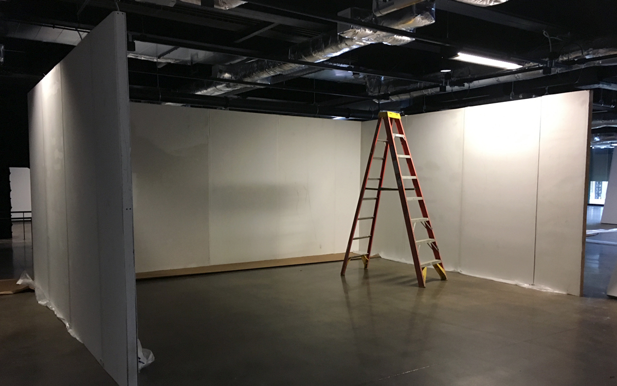 Installation shot of rental gallery display walls with truss lighting in urban setting