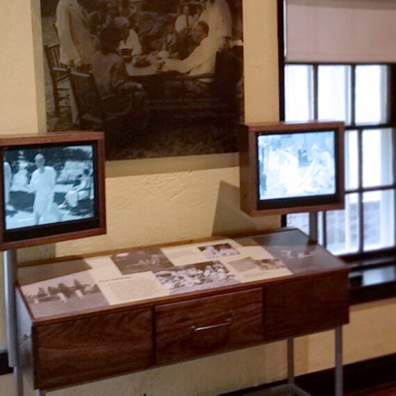 Custom interactive kiosk and display case with two monitors that play videos about FDR's life in the Eleanor Roosevelt Cottage