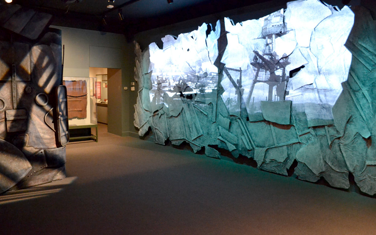 Museum exhibit wall projection on custom fabricated dimensional wall and ship for the Day of Infamy by empire exhibits in new york