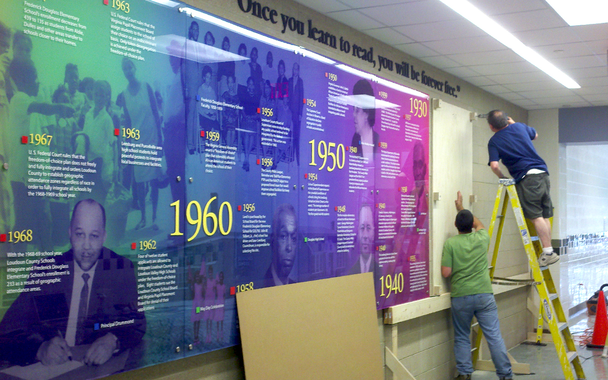 Two men installing graphic wall panel timeline in school