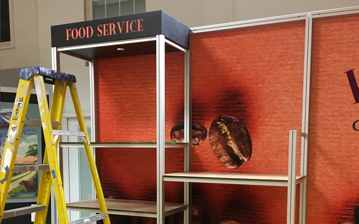 Trade Show Exhibit Booth with fabric graphics on an aluminum frame and shelving.