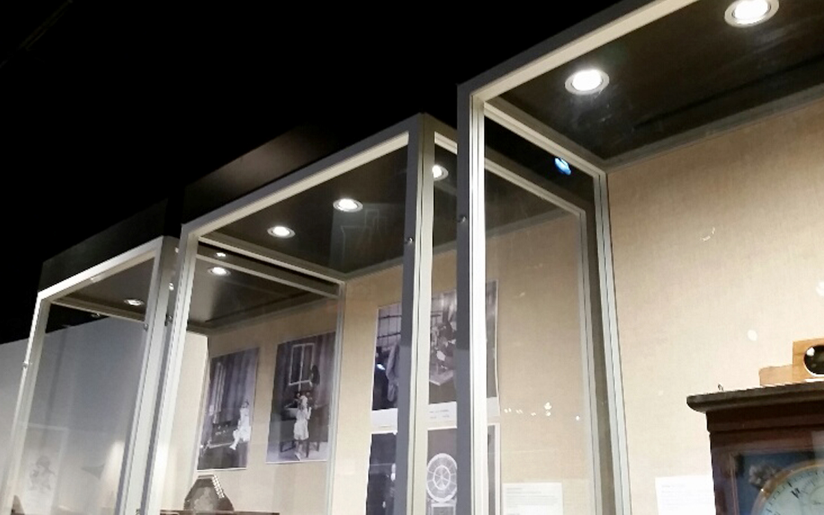 Hidden puck lighting in custom display cases built with metal rails and clear acrylic