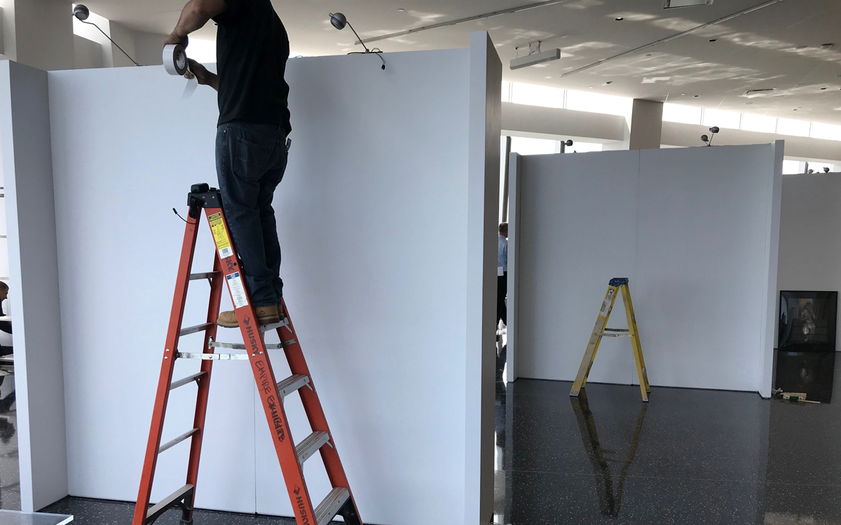 Rental gallery walls being installed by man on ladder