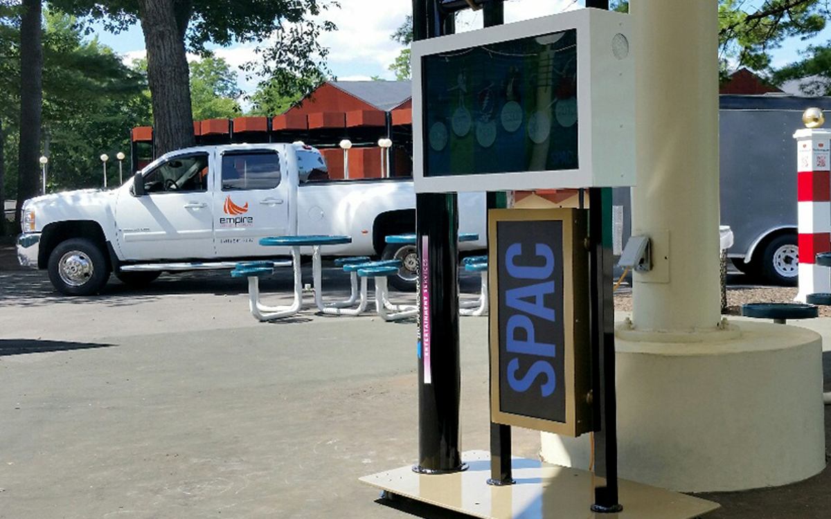 Custom kiosk for SPAC with monitor, LED lighting and acrylic roof in front of Empire truck