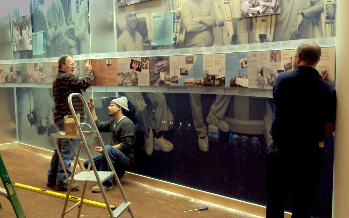 Crew installing curved timeline over custom wall mounted photo graphics of doctors
