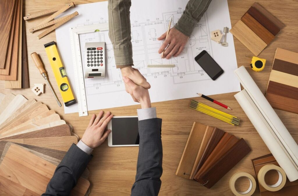 Shaking hands with client at desk covered with sample materials and architectural drawings.