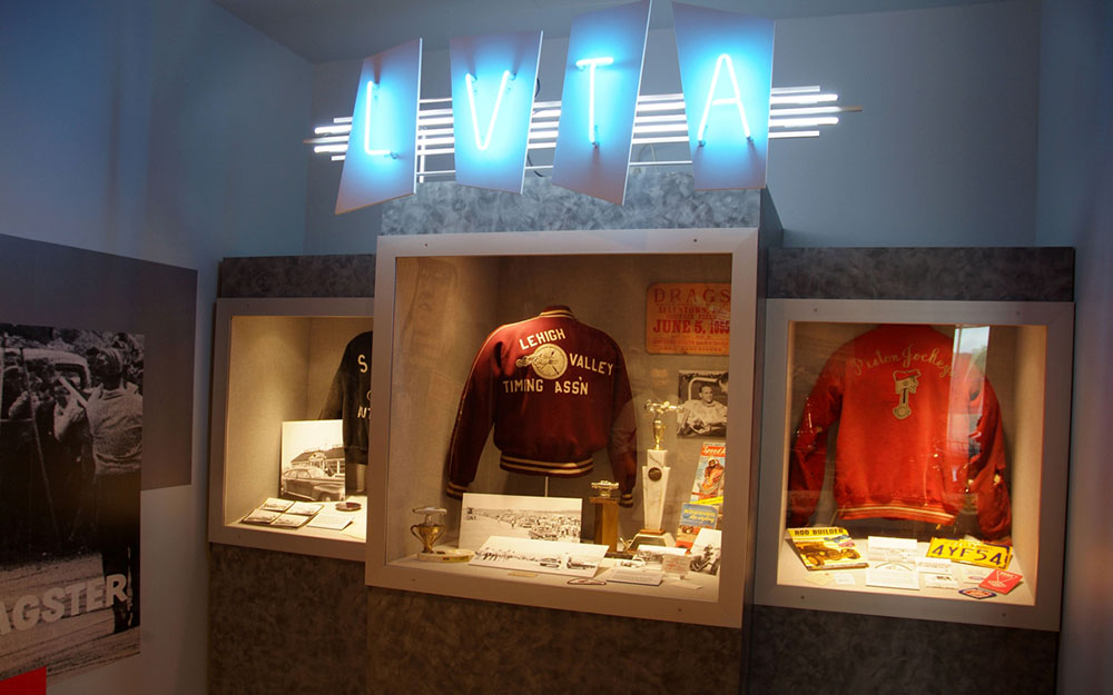 Custom neon lights with displays cases holding trophies and jackets for the America on Wheels Museum exhibit
