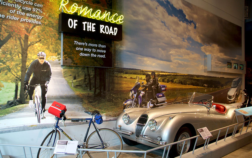 """Neon sign reading """"Romance of the Road,"""" wall graphics and reading rails for museum exhibit"""