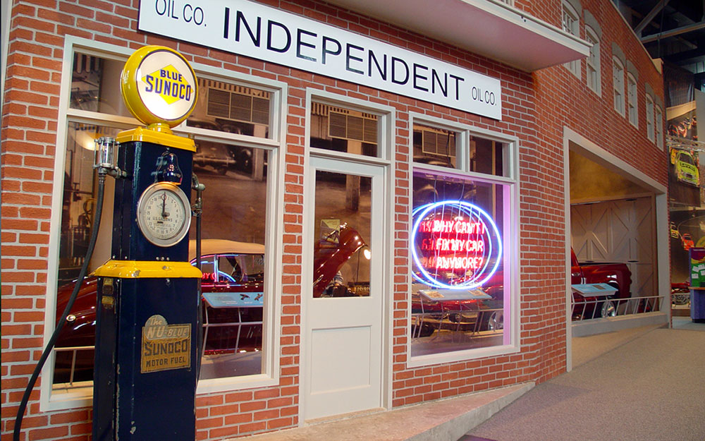 Custom fabricated brick storefront exhibit and neon sign with gas pump prop for America on Wheels