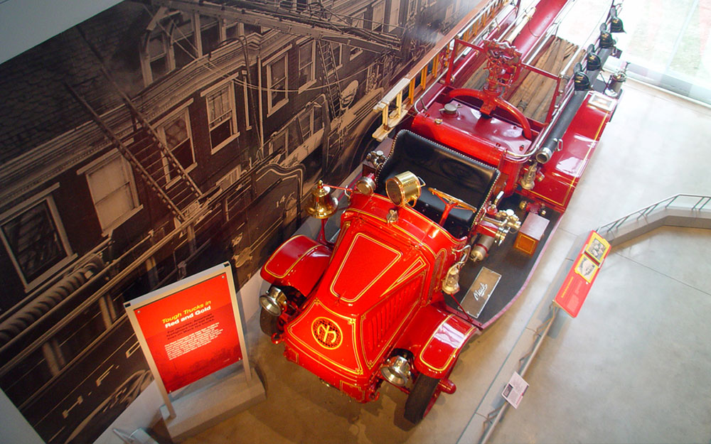 Red fire truck in front of wall graphics with interactive display