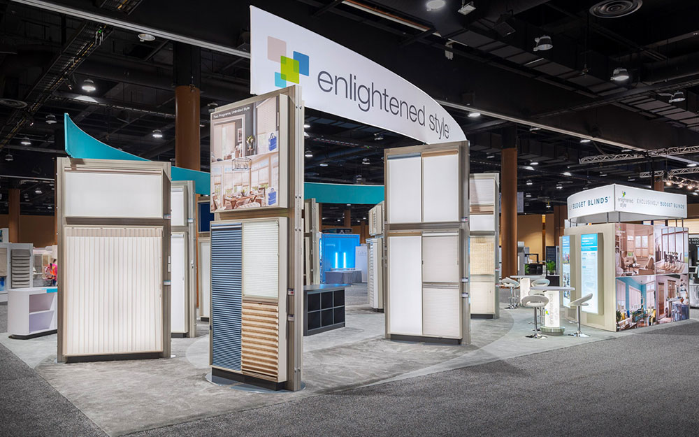Enlightened Style Trade Show Booth with view of custom blinds display, backlit rental bistro table and fabric wrapped headers