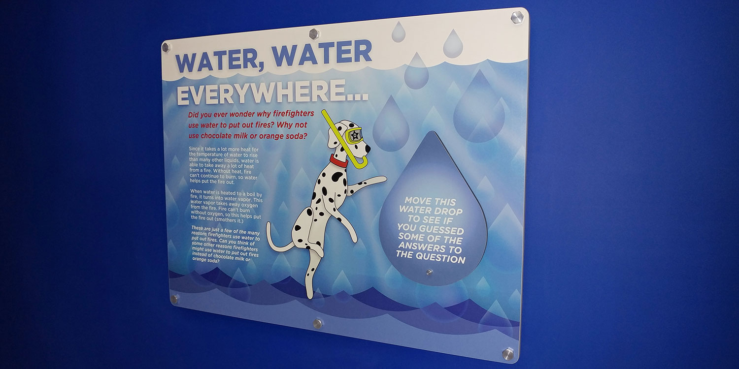 Scuba diving dog themed graphic panel with interactive elements at FASNY museum exhibition