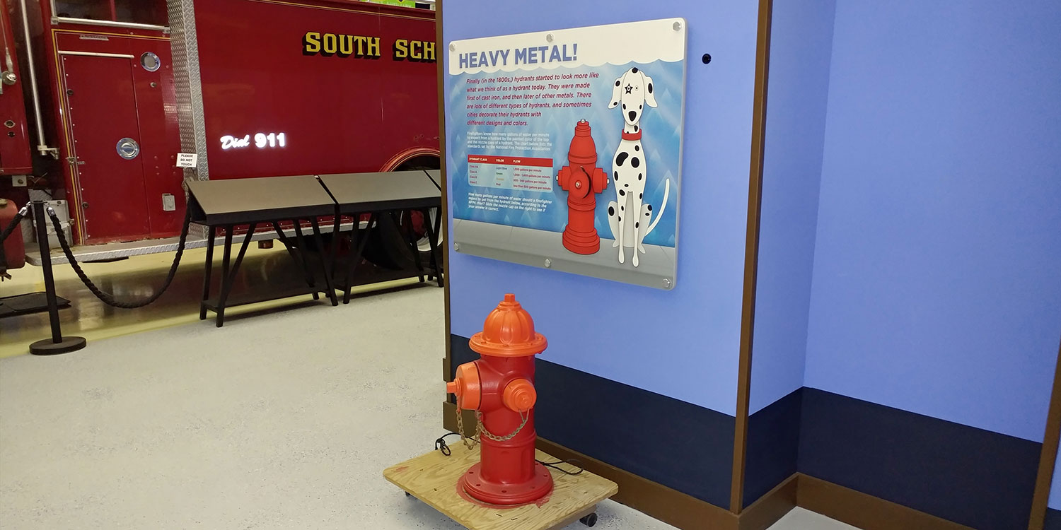 Graphic wall panel of dog with fire hydrant display for FASNY museum permanent installation
