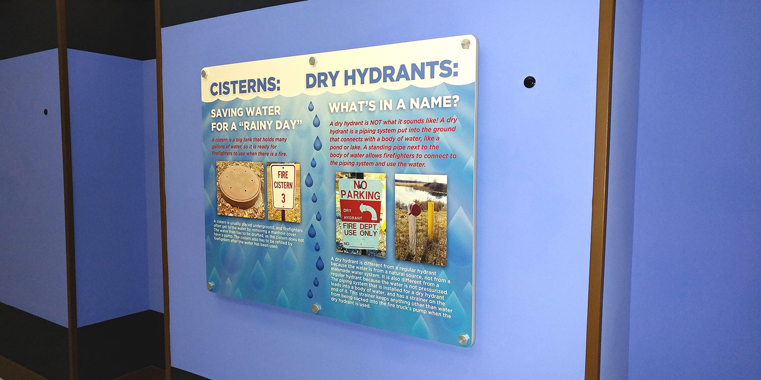 Water drop design graphic panel sign with standoffs for FASNY museum permanent installation