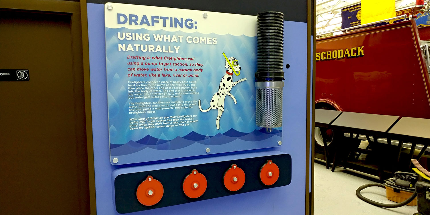 Interactive display with custom designed graphic panel with water droplet and Dalmatian cartoon theme, wall mounted with standoffs