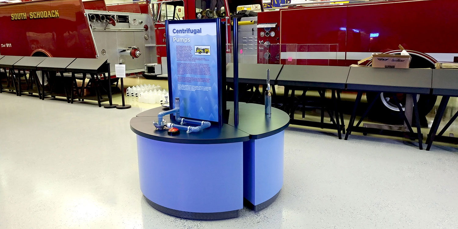 Interactive kiosk with graphic panel and firetrucks behind