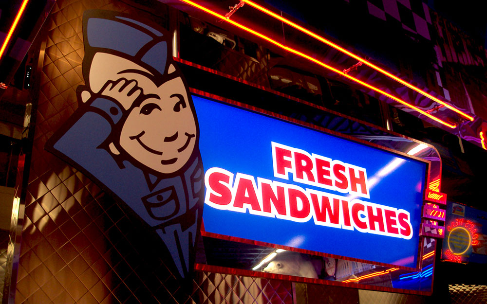 Fresh sandwiches sign with cartoon and neon lighting for Flory's Deli