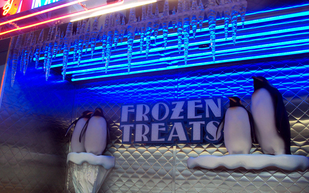 Store fixture for Flory's Deli Frozen Treats sign including neon lights, penguins and backlit icicles