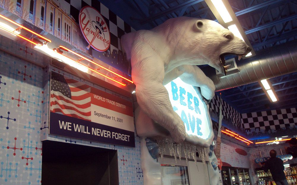 Store fixture for Beer Cave with roaring polar bear prop and neon lights at Flory's Deli
