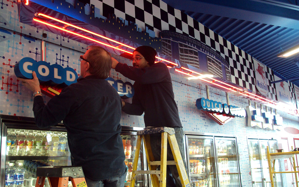 Two men installing custom lighted dimensional letters at Flory's Deli