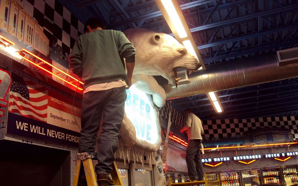 Two men installing graphics at Flory's Deli around a polar bear prop at Flory's Deli