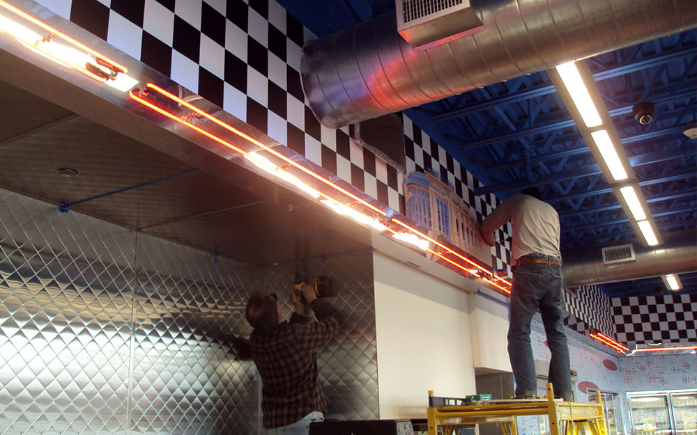 Two men installing custom cut graphic panels and chrome wall panels at a 1950s themed deli