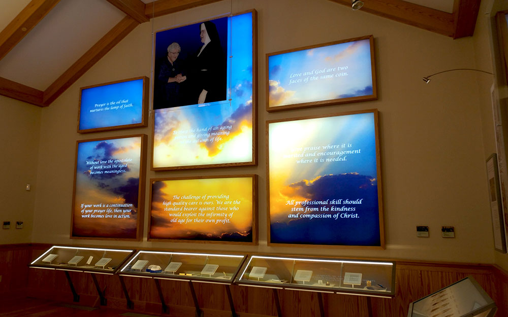 lightbox graphic wall panels and hanging scrim graphic with custom lighted display cases holding artifacts