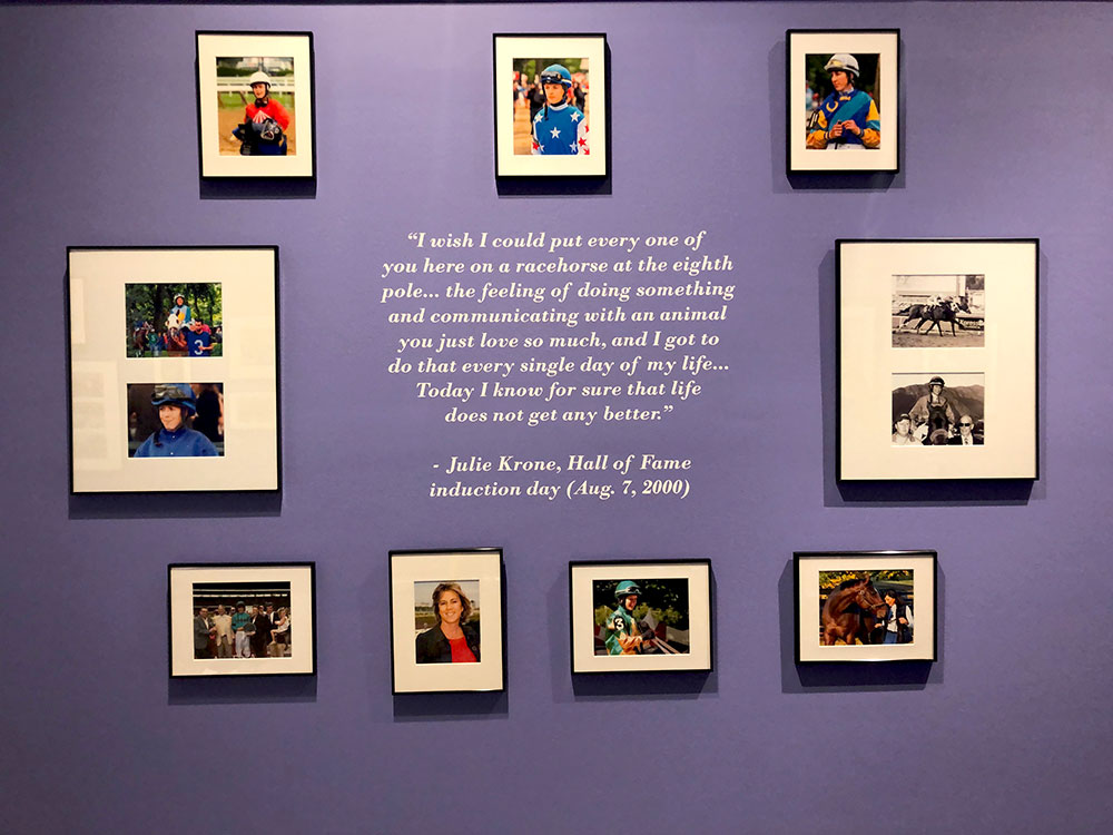 Museum exhibit purple wall with hanging framed photos and applied wall lettering with a quote from Julie Krone on Hall of Fame induction day