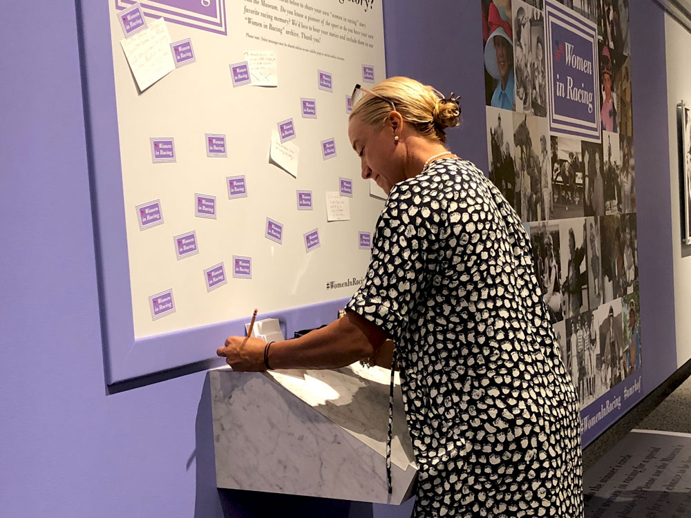 Women writing at podium in the National Museum of Racing exhibit