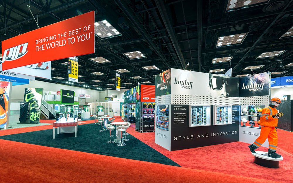 Trade show booth exhibit for PIP with mannequins on pedestals, custom built storage table, fabric wrapped header and graphic wall storage rooms
