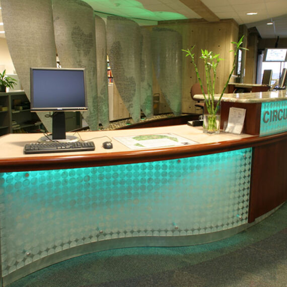 Custom built desk with backlights and sail room dividers with teal lights in the Folsom Library at RPI