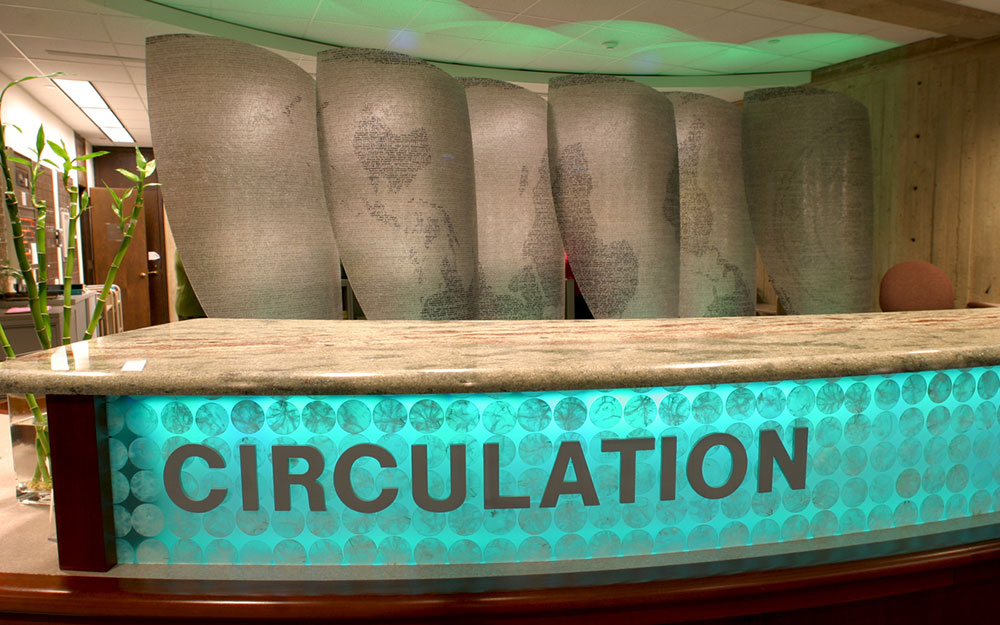 Custom built circulation desk with backlights and sail room dividers with teal lights in the Folsom Library at RPI