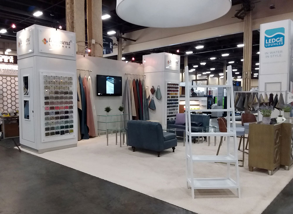Trade show booth with custom built display wall and towers with racks and sample walls, casual seating and round hanging sign