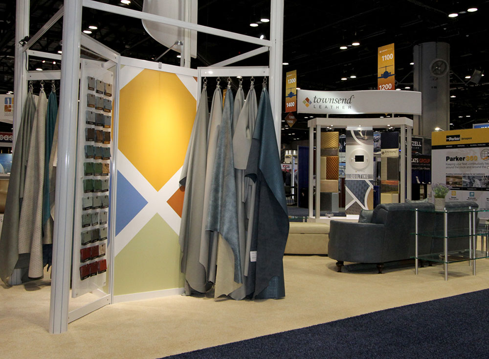 Custom built product display tower with graphics, floating sample wall and hanging rack for products, used in a trade show booth for Townsend Leather