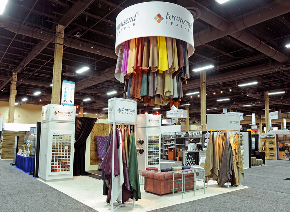 Trade show exhibit booth with purple chair display, leather chandelier, seating, custom lighting and sample racks for Townsend Leather